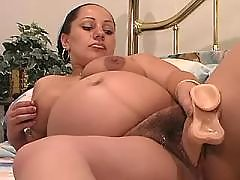 Pregnant woman plays with fat dildo