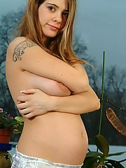 A pregnant girl is posing naked in front of a big window